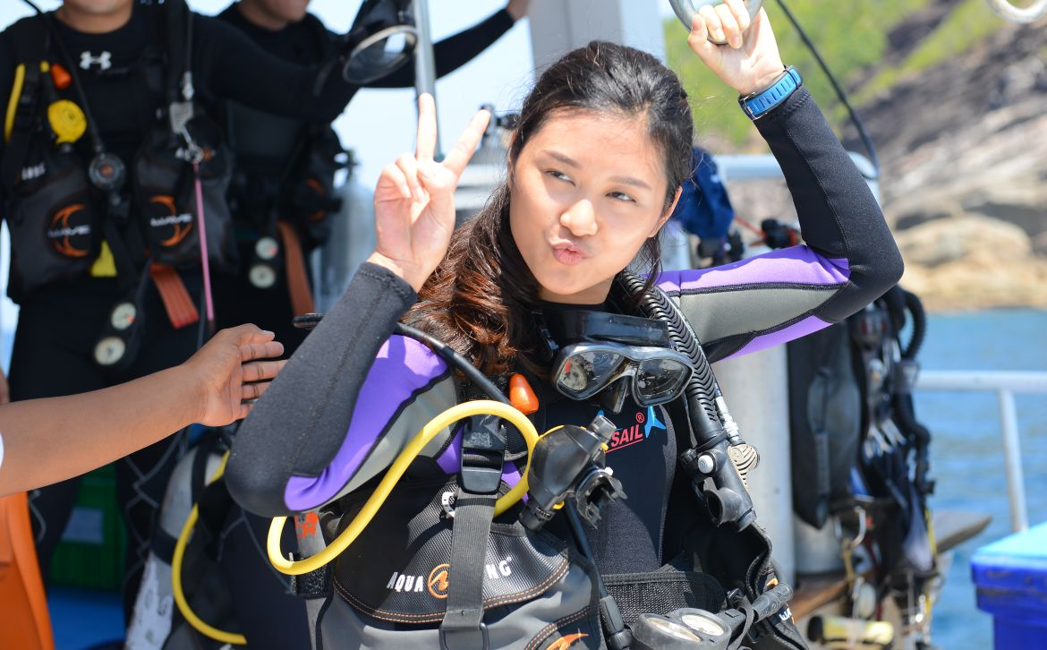 young asian female diver gives peace sign before diving in